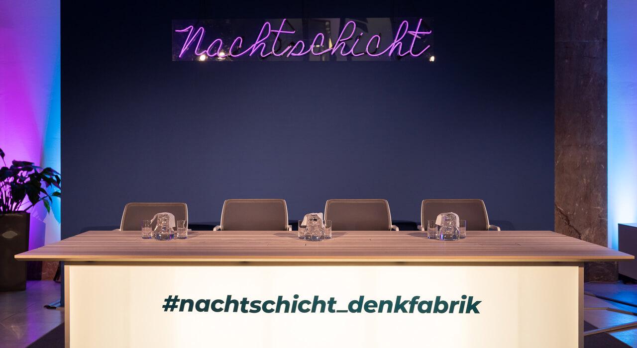 Das Podium der Nachtschicht-Diskussionsreihe in der Denkfabrik des BMAS mit der Nachtschicht-Leuchtschrift im Hintergrund.