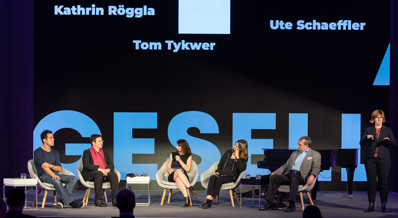 Panel with Tom Tykwer, Ute Schaeffer, host Geraldine de Bastion, Kathrin Röggla and Prof. Dr. Thomas Macho as well as sign language interpreter Dina Zander-Tabbert (f.l.t.r.)