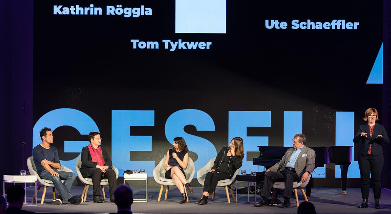 Gesprächsrunde mit Tom Tykwer, Ute Schaeffer, Moderatorin Geraldine de Bastion, Kathrin Röggla und Prof. Dr. Thomas Macho sowie Gebärdendolmetscherin (v.l.n.r.)