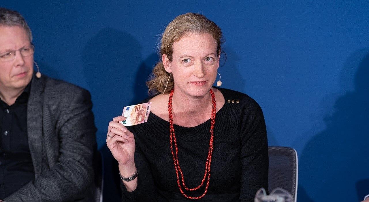 Lisa Nienhaus zeigt einen Geldschein während sie spricht