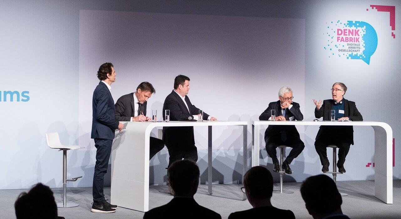 "Teilnehmer*innen des Panels zum Thema ""A European Approach to Human-centered AI"" (v. l. n. r. Ulrik Knudsen (OECD), Hubertus Heil (BMAS), Khalil Rouhana (EU), Joanna Bryson (Hertie School)) und Moderator Ali Aslan."