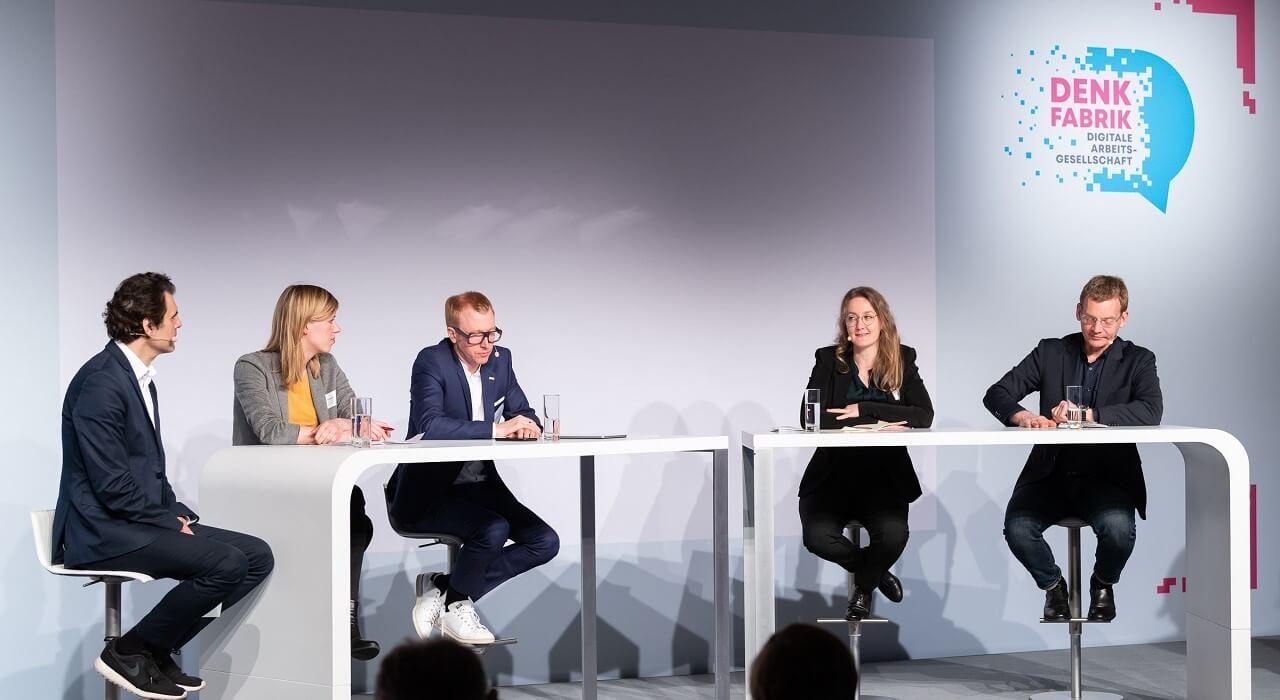 "Teilnehmer*innen des Panels zum Thema ""Safe and Trustworthy AI"" (v. l. n. r. Carla Hustedt (Bertelsmann), Dr. Joachim Bühler (TÜV), Prof. Dr. Dr. Frauke Rostalski (Uni Köln), Matthias Spielkamp (AlgorithmWatch)) und Moderator Ali Aslan."