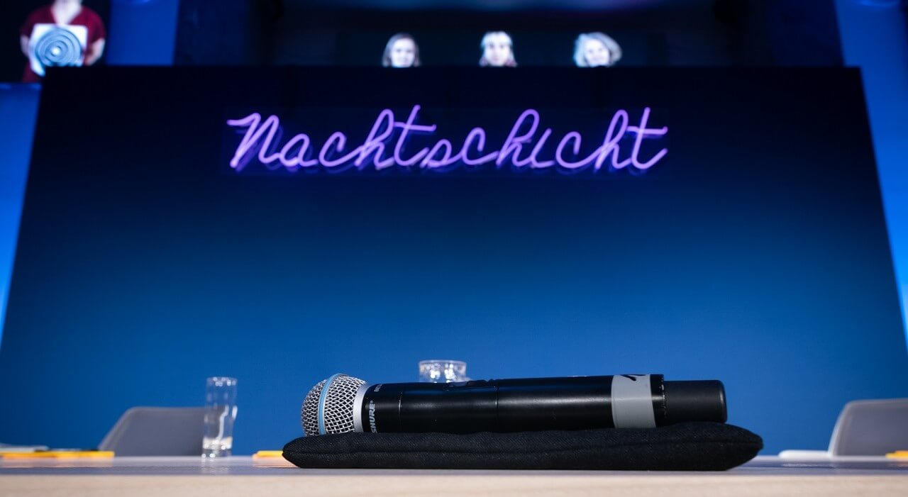 The microphone on the podium with the Nachtschicht logo in the background