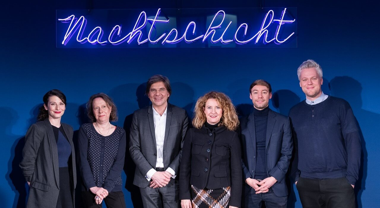 The speakers and moderators in front of the Nachtschicht logo