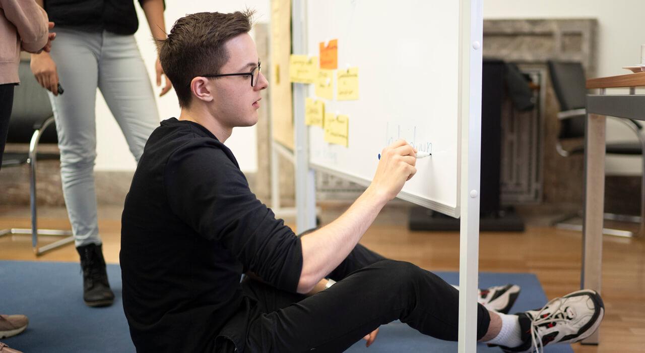 Ein Teilnehmer schreibt etwas auf eine Tafel