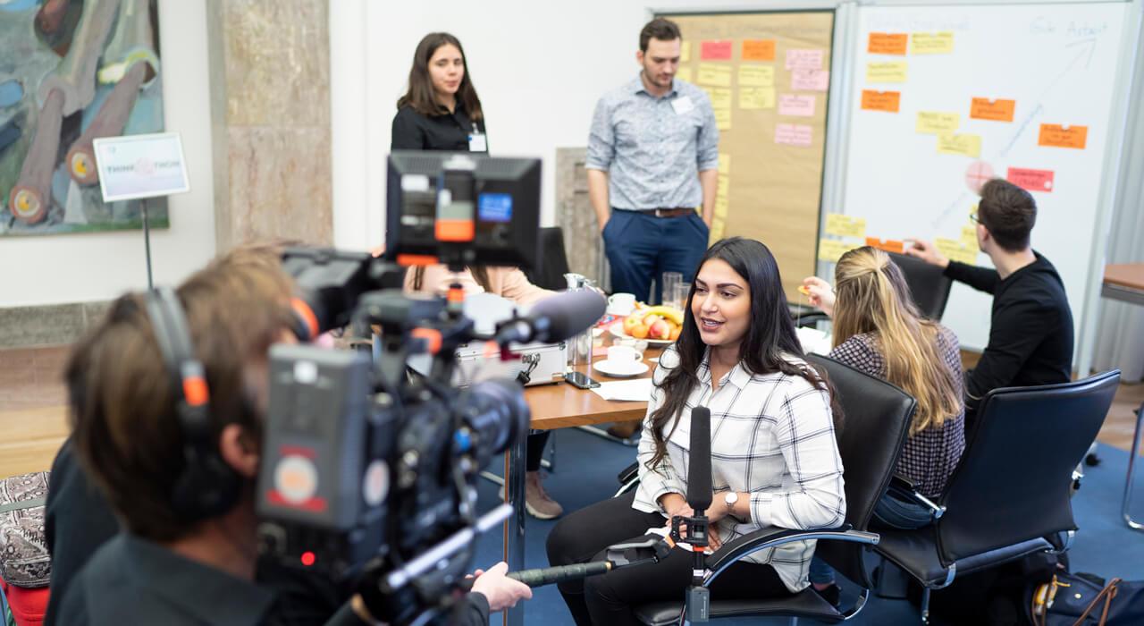 Eine Teilnehmerin spricht sitzend vor einer Kamera in ein Mikrofon