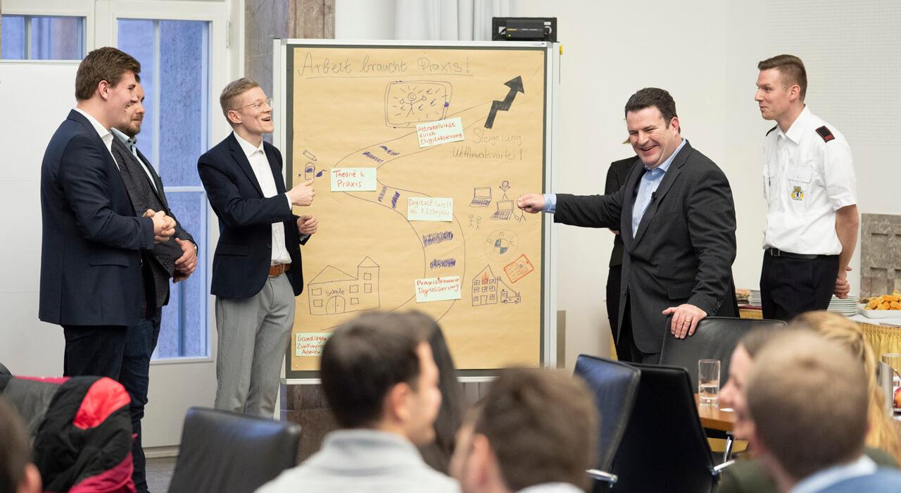 Minister Hubertus Heil mit Teilnehmenden am Flipchart