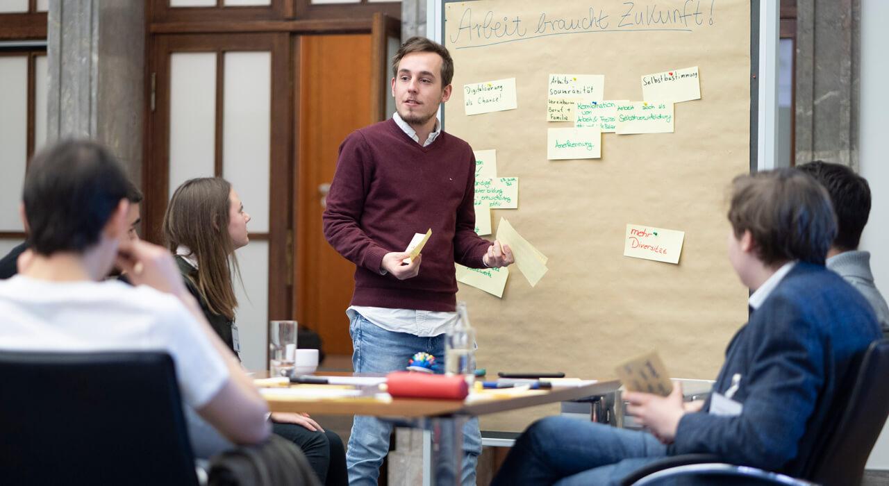 Ein Teilnehmer redet vor einem Flipchart