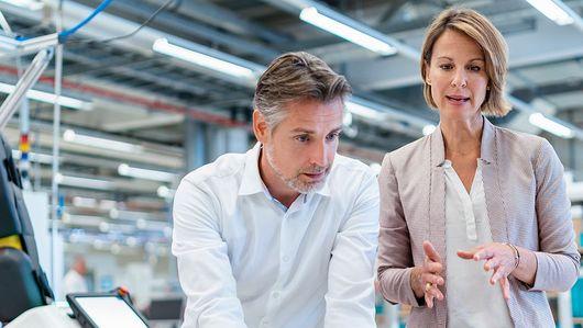 Zwei Mitarbeitende stehen neben einem Roboter-Greifarm und tauschen sich aus.. Öffnet Seite: : 11 KI-Projekte für die betriebliche Praxis