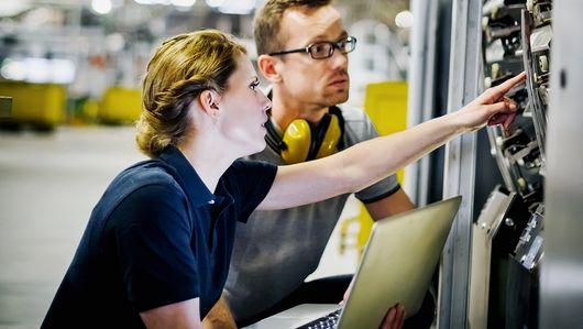 Eine Frau mit einem Laptop in der Hand zeigt einem Mann die Bedienung einer Maschine. . Öffnet Seite: : Digitale Kompetenzen in innovativen Technologien im Fokus