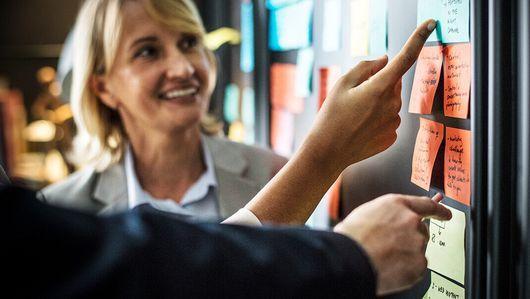 """Eine Frau und andere Personen an einer Pinnwand.. Öffnet Seite: : Fokusgruppe """"Künstliche Intelligenz in der Arbeitswelt"""""""